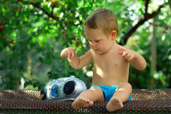 Baby DJ playing with retro recorder in garden. Cute baby DJ playing with retro recorder in the garden, sitting on rusty bed frame Stock Images