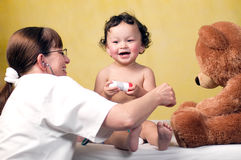 Baby with doctor. Cheerful baby at the doctor,playing with toy bear Stock Photo