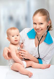 Baby and doctor pediatrician. doctor listens to the heart with s. Baby at the doctor pediatrician. doctor listens to the heart with a stethoscope Stock Image