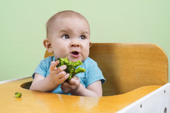 Baby doesn't like broccoli. Funny baby doesn't like broccoli Royalty Free Stock Photo