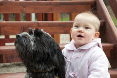 Baby and dog. Portrait of a black and gray dog and a happy baby girl in a ping coat in an outdoor playground; both are looking up Stock Photography