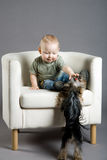 Baby with dog. Photo of the baby sitting in an armchair with a small dog Stock Photography