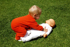 Baby with doll. A full body of a beautiful blond caucasian white baby girl trying to pick up her big doll from the lawn with her little hands and playing with it Stock Images