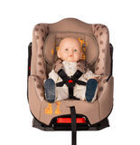 Baby doll in a booster seat for a car Royalty Free Stock Photos