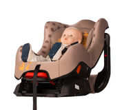 Baby doll in a booster seat for a car Royalty Free Stock Photo