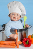 Baby Doll with chef's hat. Baby Doll sitting with chef hat in a cooking pot on Blue Background Stock Photography