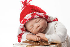 Baby Doll with Christmas Cap. Christmas Baby Doll Boy with Knit Cap sleeping on Gift Box Royalty Free Stock Photography