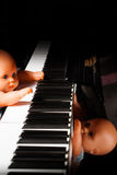 Baby doll playing piano Royalty Free Stock Photos