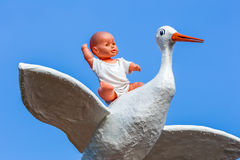 Baby doll sitting on back of stork with blue sky Stock Photos