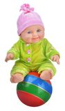 Baby doll sitting on striped beach ball Stock Image