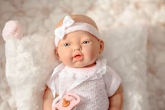 Cute Baby Doll in white pale clothes  on beige background. Baby doll in white pale clothes  on beige  background royalty free stock photos