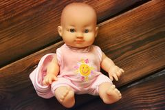 Baby doll on wooden background. Doll. A toy stock photo