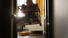 Baby in doorway swing stock video