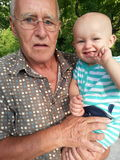 Baby draußen mit Großvater stockfoto