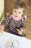 Baby drawing. A baby girl sitting at a table and drawing Royalty Free Stock Image
