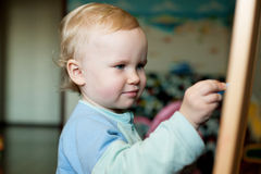 Baby drawing chalk on a blackboard Royalty Free Stock Images