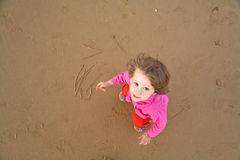Baby draws on beach Stock Images