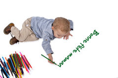 Baby draws with crayons bonne fetes maman Stock Photo