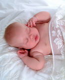Baby Dreams. Closeup of sleeping baby on white comforter with lace coverlet Stock Images