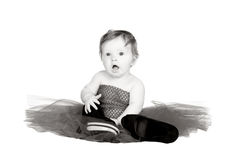 Baby with  dress in black and white. Baby sitting in red dress playing with shoes in black and white Stock Photo