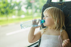 Baby in dress drink water ride bus Stock Photography