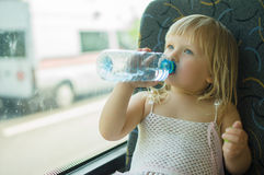 Baby in dress drink water ride bus Stock Image