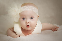 Baby in a dress lies on a pillow Royalty Free Stock Image