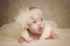 Baby in a dress lies on a pillow Stock Photo