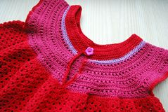 Baby dress is red. Manual work. Connected with love. Hobby-knitting. Close up stock image