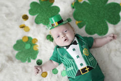 Baby dressed up for St Patricks Day. A young baby dresses up for st patricks day with an outfit that says Kiss Me!  and a irishmans hat Royalty Free Stock Photography