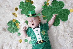 Baby dressed up for St Patricks Day. A young baby dresses up for st patricks day with an outfit that says Kiss Me!  and a irishmans hat Royalty Free Stock Photo