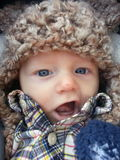 Baby Dressed Warmly. Baby with blue eyes wearing a fuzzy knit hat and a plaid shirt with a funny expression with a small scratch on his nose Royalty Free Stock Photography