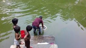 Baby drie kijkt vis hoe te om vissen in een vijver te spelen stock foto's