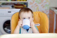 Baby drink from baby cup Royalty Free Stock Images