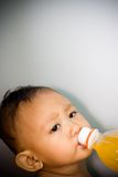 Baby drink orange juice royalty free stock images