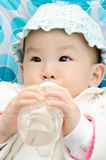 Baby drink water. From bottle stock image