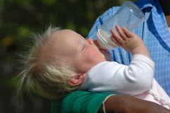 Baby drinking bottle. A blond white caucasian baby girl lying in the black arms of an African American woman holding a bottle of milk in her little hands and Royalty Free Stock Photos