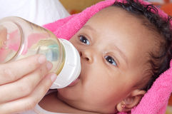 Baby drinking a bottle. Adorable baby drinking a bottle - focus in the face Stock Photography