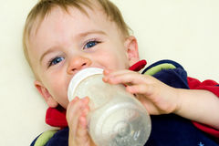 Baby drinking bottle. Baby boy drinks bottle in crib Royalty Free Stock Images
