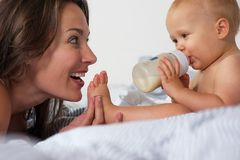 Baby drinking from bottle with mother smiling Stock Images