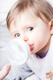 Baby drinking from a bottle. Portrait of a cute baby boy drinking from a bottle Royalty Free Stock Photography