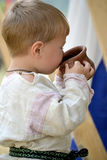 Baby is drinking from a cup Stock Photo