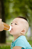 Baby drinking fruit juice. Baby boy is drinking fruit juice in outdoor Royalty Free Stock Photos