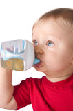 Baby drinking juice from bottle Stock Photo