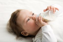 Baby drinking milk. A baby eating milk from the bottle Royalty Free Stock Photos