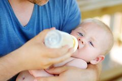 Baby drinking milk from bottle Stock Photo