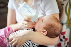 Baby drinking milk from bottle Stock Photos