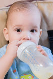 Baby drinking milk from a bottle in the apartment. Baby drinks from a bottle of milk in the house Royalty Free Stock Photography