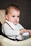 Baby drinking milk from a bottle in the apartment Stock Photography