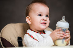 Baby drinking milk from a bottle in the apartment Royalty Free Stock Photography